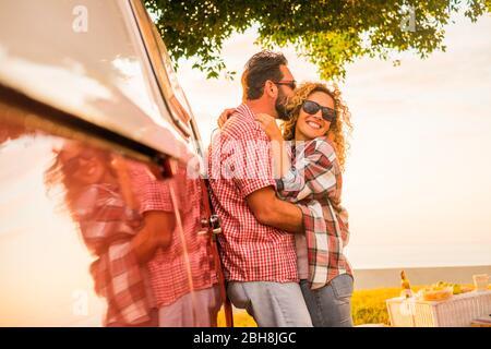 Amor y concepto de estilo de vida casado para la hermosa pareja caucásica de viajeros abrazándose y besándose con la furgoneta roja vintage - espejo y alegre gente feliz disfrutando de la actividad de ocio al aire libre juntos