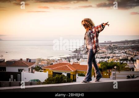 Mujer sonriente caminar en equilibrio sobre una hermosa ciudad costa vista al océano durante la puesta de sol - libertad e independencia concepto de felicidad para la gente de edad media que disfruta de actividades de ocio al aire libre sobre las casas