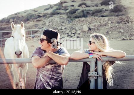 Pareja de jóvenes caucásicos niño y niña dentro de la caja de caballo con blanco hermoso animal en el fondo - la amistad y disfrutar de la naturaleza al aire libre concepto