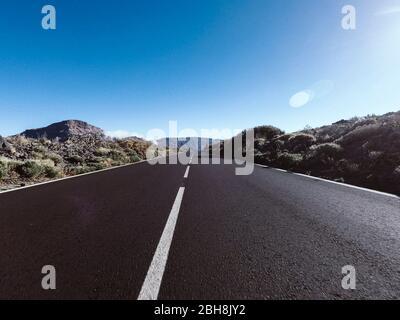 Camino largo en la montaña con montajes en frente y efecto de luz solar - punto de vista del suelo con asfalto negro y líneas blancas - concepto de conducción y viaje