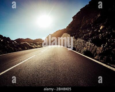 Camino largo en la montaña con sol en frente y efecto de luz solar - punto de vista del suelo con asfalto negro y líneas blancas - conducción y concepto de viaje