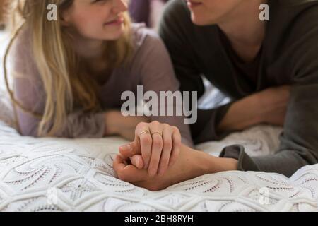 Pareja cariñosa sosteniendo las manos acostadas una sobre otra