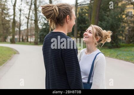 Feliz pareja joven con dreadlocks sosteniendo las manos y riendo con una mujer joven bonita al aire libre en un jardín Foto de stock