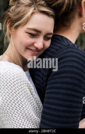 Feliz amante joven moderno pareja con dreadlocks profundamente en el amor de pie al aire libre abrazándose uno al otro en un abrazo de cerca y riendo en un retrato de cerca Foto de stock