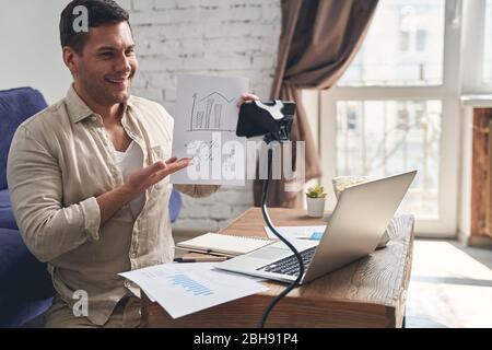 Blogger sentado frente a la cámara del teléfono móvil