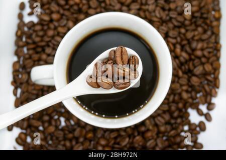 taza de café blanco, cuchara y granos de café asados que se aislaron sobre fondo blanco. vista superior.