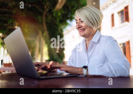 Mujer mayor segura escribiendo texto en un ordenador portátil en un café