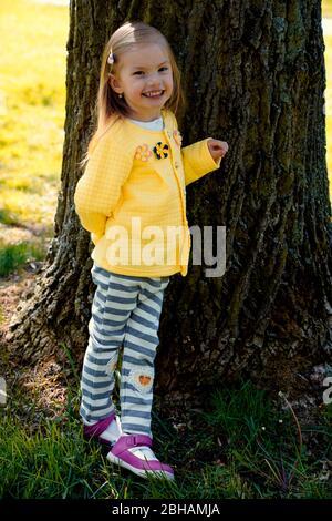niña apoyada contra el tronco de un árbol viejo