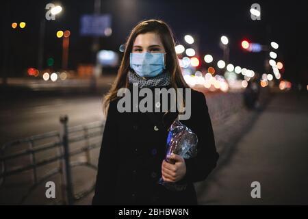 Retrato de una joven feliz mujer con máscara médica cara llevando pan mientras camina por la calle de la ciudad por la noche