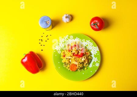 Paella con calamar: Plato tradicional español con especias y verduras sobre fondo amarillo.