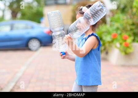 Niña pequeña sosteniendo botellas de agua de plástico para reciclaje. Concepto de mundo libre de plástico, el futuro para nuestros niños. Cero residuos.