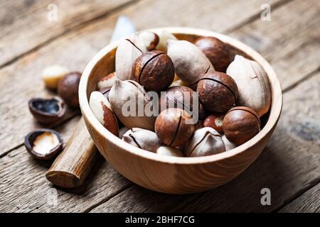 Nueces mixtas secas en un cuenco de madera de primer plano. Nueces de macadamia, pacán y Brasil con cuchillo sobre mesa de madera. Disparo macro de estudio.
