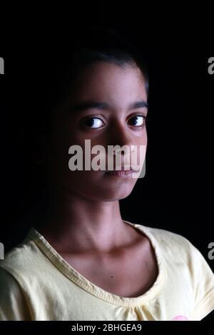 Retrato de una niña India con pelo corto. Hermoso ojo de un niño sobre fondo negro. Aspecto dramático de una niña en la India.