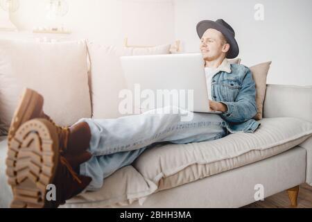 Hombre joven hombre de negocios en sombrero está soñando con negocios, éxito y dinero. Concepto de descuido, inicio, viaje de vacaciones