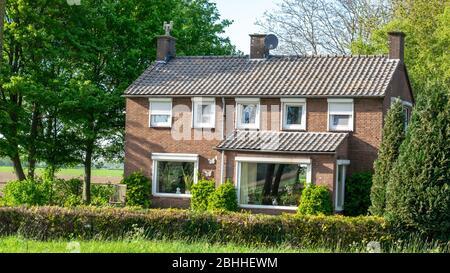 Una típica casa holandesa de edad que se encuentra en un paisaje de polder holandés junto a los árboles