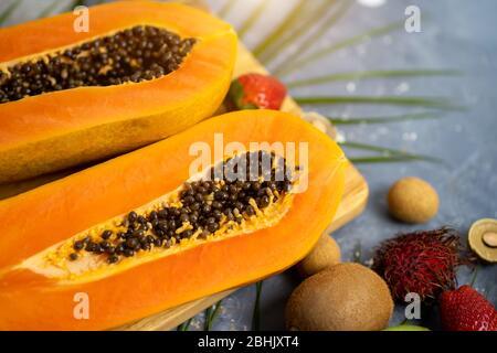 Papaya. Frutas tropicales. Primer plano de dos mitades de papaya madura con semillas sobre tabla de corte de madera. Papaya en rodajas y otras frutas exóticas sobre la mesa