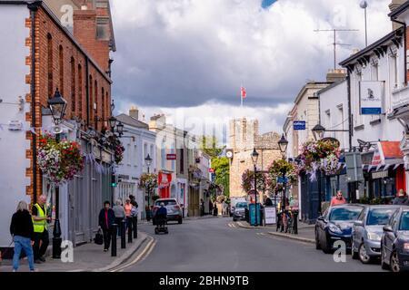 Calle principal con muchas tiendas y pubs en Dalkey, Irlanda. Peatones haciendo compras y coches aparcados y conducidos a lo largo de la calle. Foto de stock