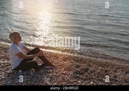 Mujer madura sentada después de correr en la playa al atardecer. Correr por la noche