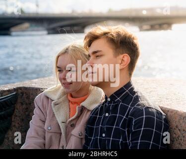 Los adolescentes enamorados se sientan en la costa en el centro de la ciudad, descansando bajo el sol de otoño. Concepto el primer amor adolescente, el comienzo de las relaciones. Un niño Foto de stock