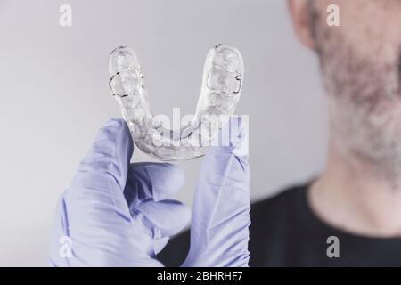 Mano con guante azul sosteniendo una férula dental, mirando a un hombre adulto frente al fondo blanco