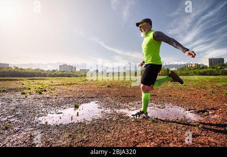 Hombre con barba gris que se ejecuta en el sendero sucio con salpicaduras de agua en el fondo de montaña en la mañana. Concepto de estilo de vida saludable