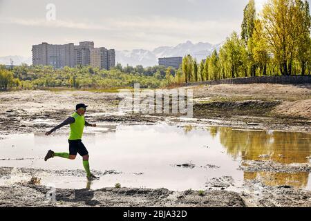 Hombre con barba gris que se ejecuta en el sendero sucio con piscina en el fondo de montaña en la mañana. Concepto de estilo de vida saludable