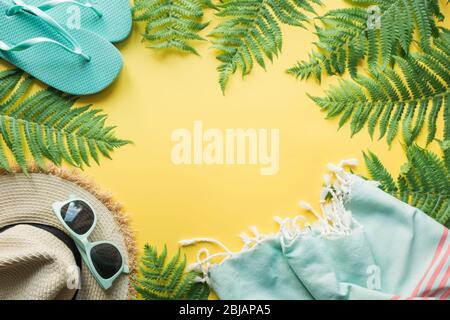 Borde de traje de playa accesorios femeninos. Vacaciones tropicales, sombrero de paja, toalla, hojas de helecho en amarillo. Concepto de verano. Vista superior con espacio para te