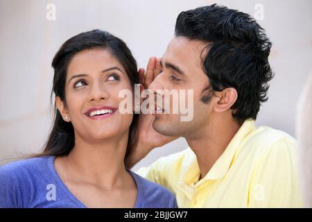 El hombre susurrando en un oído femenino Foto de stock