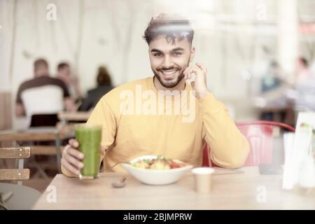 Joven sentado en la mesa del restaurante, comiendo ensalada