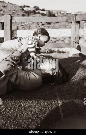 Mujer acostada en la hierba sosteniendo a su hijo, con su esposo cerca de ella, al atardecer. Foto de stock