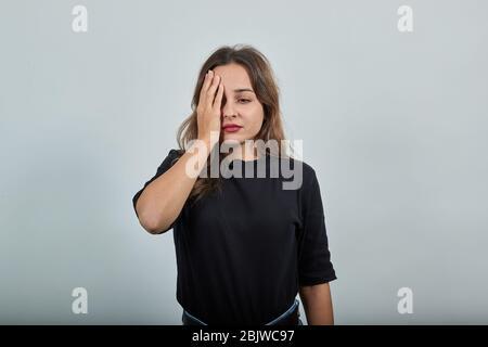 Niña disgustada en una depresión, con mal humor toca su mano a cara