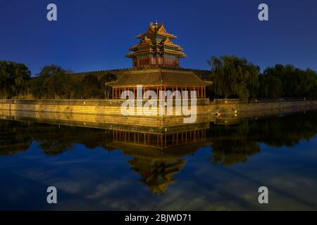 Torre noroeste del Museo del Palacio de la Ciudad Prohibida en Beijing, China, que se refleja en el foso de agua por la noche Foto de stock