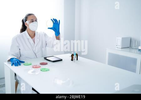Investigadora o científica joven que examina la solución en un plato de Petri en un laboratorio. El investigador está analizando la innovación relacionada con la medicina. BI