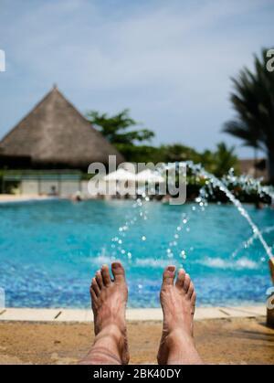 pies descalzos de un hombre tomando un baño de sol en una piscina con fuentes y una cabaña en el fondo vertical