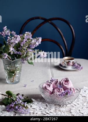 Zephyr casero dulce violeta atmosférico o Marshmallow de grosella negra cerca de las flores lilas y taza de café en tela gris de la mesa y backgroun oscuro