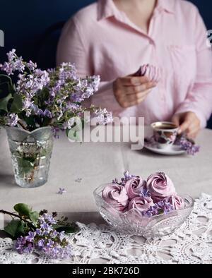 Mujer bebiendo café con Zephyr casero dulce violeta o Marshmallow de grosella negra cerca de flores lilas sobre tela gris de la mesa y fondo oscuro