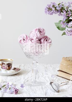 Zephyr casero dulce violeta o Marshmallow de grosella negra cerca de flores lilas, libros viejos y taza de café en tela blanca de la mesa y fondo blanco
