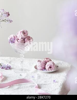 Zephyr casero dulce violeta o Marshmallow del grosella negra alrededor de las flores lilas en tela blanca de la tabla y fondo claro