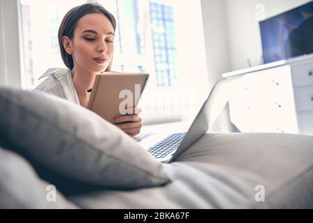 Estudiante femenina inteligente caucásica que estudia desde casa