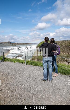 Pareja joven mirando hacia la hermosa cascada en Islandia mientras está de vacaciones.