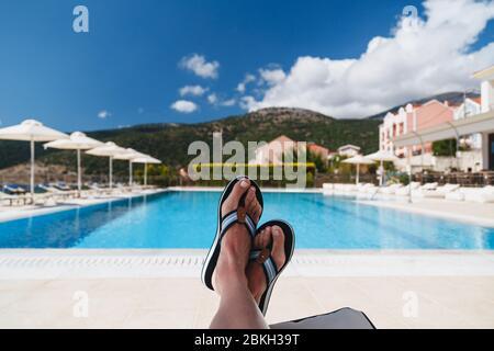 Odyssey Hotel, Agia Efimia, Cephalonia Island, Grecia - Julio, 14 2019: Vista de cerca de los pies de la joven mujer en Tommy Hilfiger chanclas azules tumbadas en un