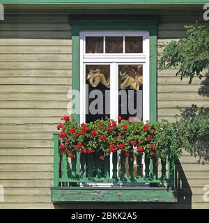 Antiguo balcón de madera con flores rojas en flor en el luminoso día de verano Foto de stock