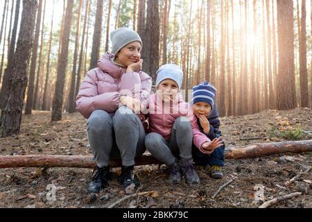 Joven adulto hermosa madre con dos adorables adorables alegre juguetón niños caucásicos, niño y niña, divertirse caminando en primavera o otoño de bosque