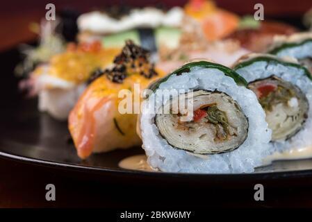 Sushi zuko maki con gambas, queso, pepino y cavilo negro de masago. Rollo de dragón casero, comida japonesa.
