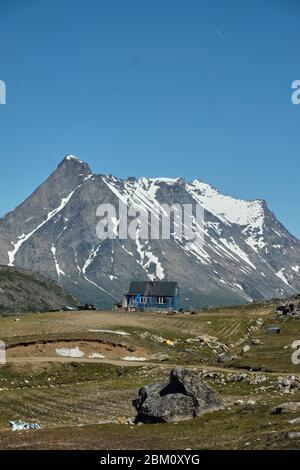 Casa solitaria cerca del pueblo groenlandés de Tasiusaq con cordilleras épicas en el fondo Foto de stock