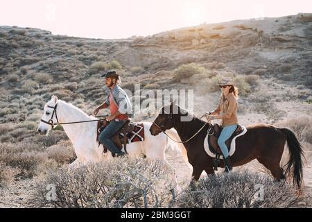 Gente joven montando caballos haciendo excursión al atardecer - pareja salvaje divirtiéndose en el tour ecuestre - Entrenamiento, cultura, pasión, estilo de vida saludable, spo