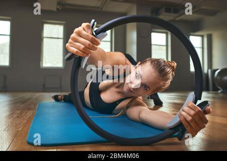 Joven modelo de fitness mujer atleta en sportswear haciendo ejercicios de estiramiento con expansor de caucho. Culturismo estilo de vida saludable concepto imagen