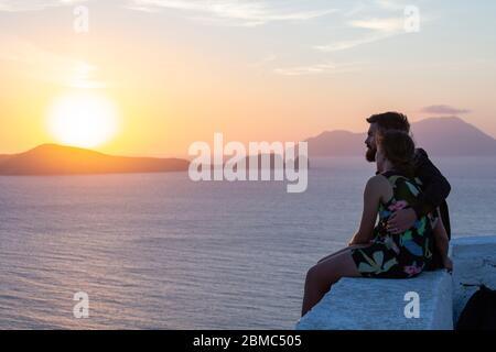 Una pareja joven disfrutando de una puesta de sol costera cerca de la Iglesia de Thalassitra, Plaka, Milos, Islas Cícladas, Grecia