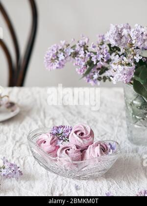Violeta dulce casero Zephyr o Marshmallow de grosella negra cerca de las flores lilas en jarrón de cristal sobre tela blanca de la mesa