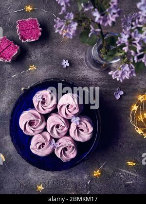 Zephyr o Marshmallow caseros dulces violeta atmosférico de grosella negra cerca de flores lilas y estrellas mágicas luces en la vista superior de fondo oscuro